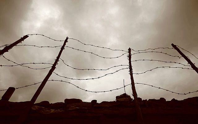 Barbed wire fence against a dark sky. (Getty Images via JTA)