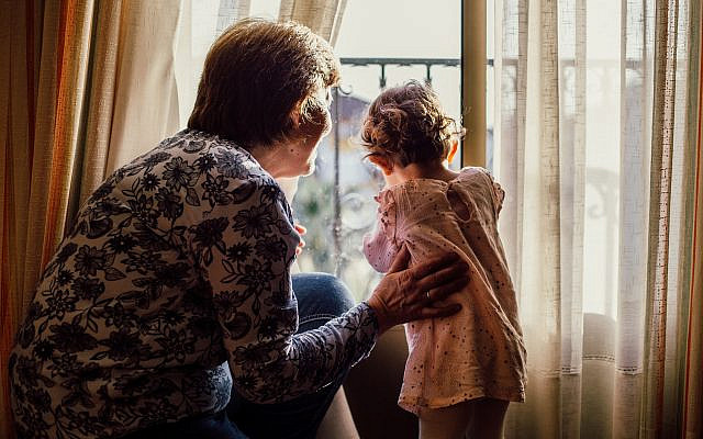 A beautiful shot of an elderly female and a baby girl looking through a window