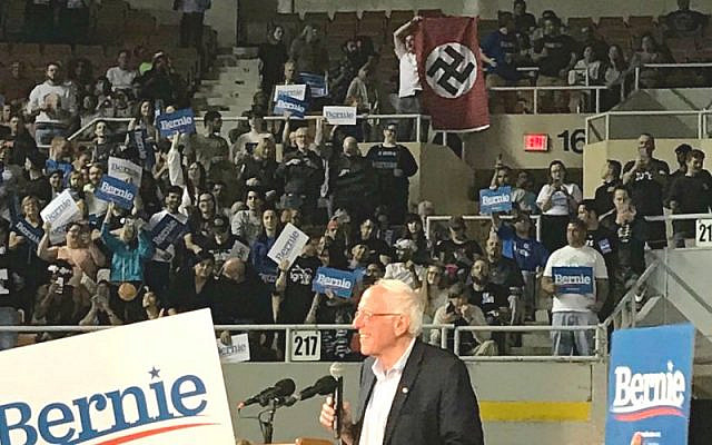 A man unfurls a swastika at a Bernie Sanders rally in Arizona on March 5, 2020. (Screencapture/ YouTube)