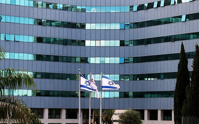 Israeli national flags flutter in front of an office tower at a business park also housing high tech companies, at Ofer Park in Petah Tikva, Israel August 27, 2020. REUTERS/Ronen Zvulun