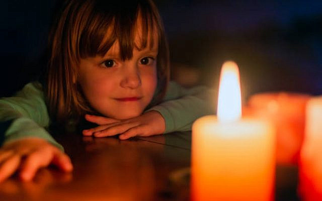 A young girl looks at a lit candle. (iStock)