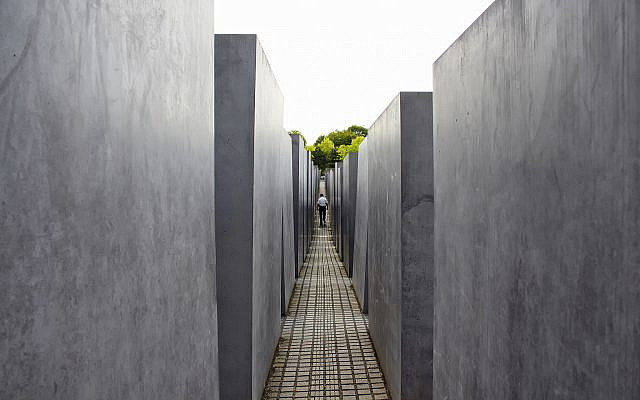 Man walks at Holocaust Memorial in Berlin Designed by architect Peter Eisenman and engineer Buro Happold. Berlin - July 1, 2016 (Stock)