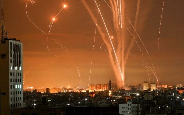 """Rockets light up the night sky as they are fired towards Israel from Beit Lahia in the northern Gaza Strip on May 14, 2021. - Israel bombarded Gaza with artillery and air strikes on Friday, May 14, in response to a new barrage of rocket fire from the Hamas-run enclave, but stopped short of a ground offensive in the conflict that has now claimed more than 100 Palestinian lives. As the violence intensified, Israel said it was carrying out an attack """"in the Gaza Strip"""" although it later clarified there were no boots on the ground. (Photo by MOHAMMED ABED / AFP)"""