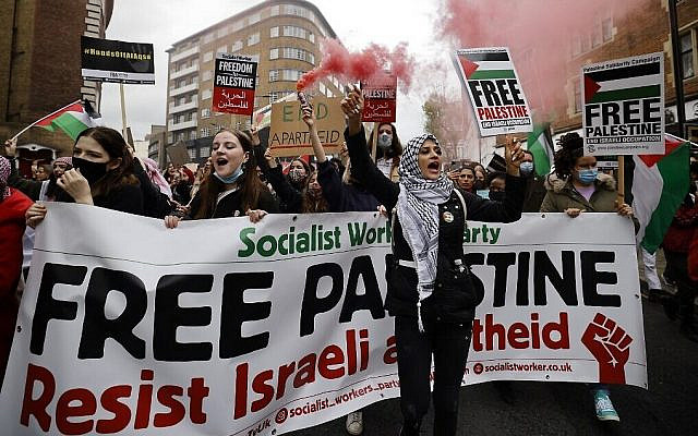 Pro-Palestinian activists and supporters in London let off smoke flares, wave flags and carry placards during a demonstration against Israel amid fighting between the Jewish state and Palestinian terrorists in Gaza, on May 15, 2021. (Tolga Akmen/AFP)