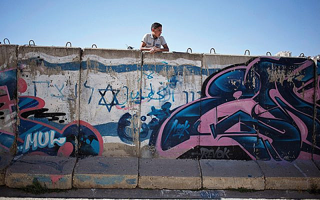 A Palestinian boy looks behind a wall separating Jewish part and Palestinian part of the West Bank. (AP Photo/Ariel Schalit) via Jewish News