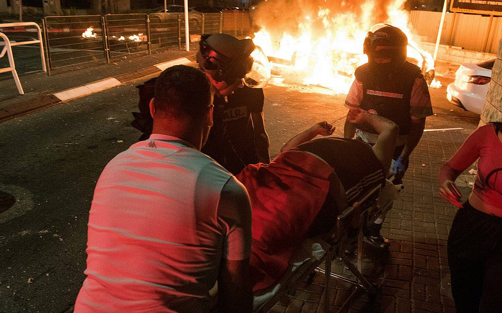Medics evacuate an injured man during clashes between Arab and Jews in Acre, northern Israel, May 12, 2021. (Roni Ofer/ Flash90)