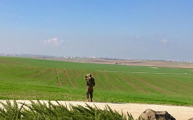An Israeli soldier looks across the border at Gaza in the distance. (Photo credit:Andrew Getraer)