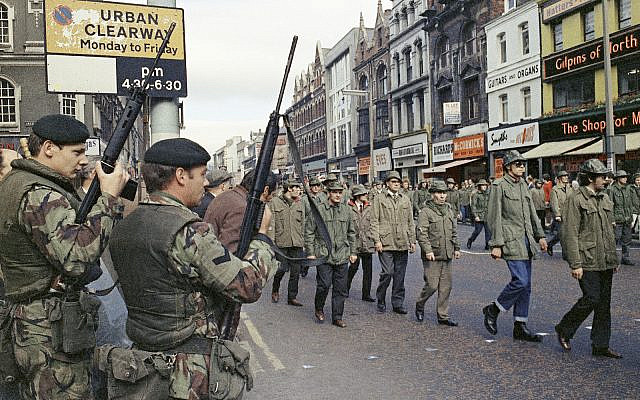 """In this Aug. 1972 file photo British troops watch as members of the Ulster Defence Association parade through Belfast, Northern Ireland during the violent 30-year Catholic-Protestant conflict known as """"The Troubles."""" (AP Photo, File)"""