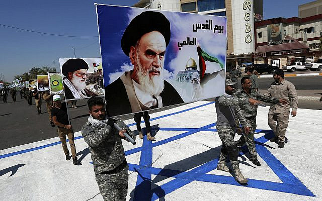 In this photo from June 23, 2017, supporters of Iraqi Hezbollah brigades march on a representation of an Israeli flag with a portrait of late Iranian leader Ayatollah Khomeini and Iran's Supreme Leader Ayatollah Ali Khamenei, in Baghdad, Iraq. (AP Photo/Hadi Mizban, File)