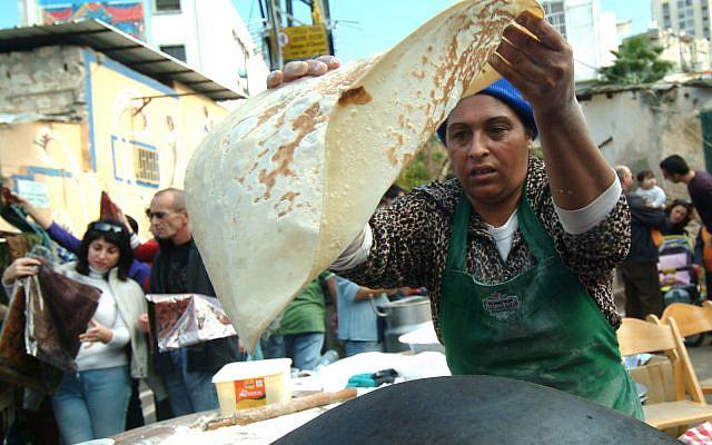 An arab woman making pita bread in a taboon stove in Wadi Nisnas market in an Arab neighborhood of Haifa during the Festival of Festivals, Dec. 22, 2007 (Jorge Novominsky/Flash90)