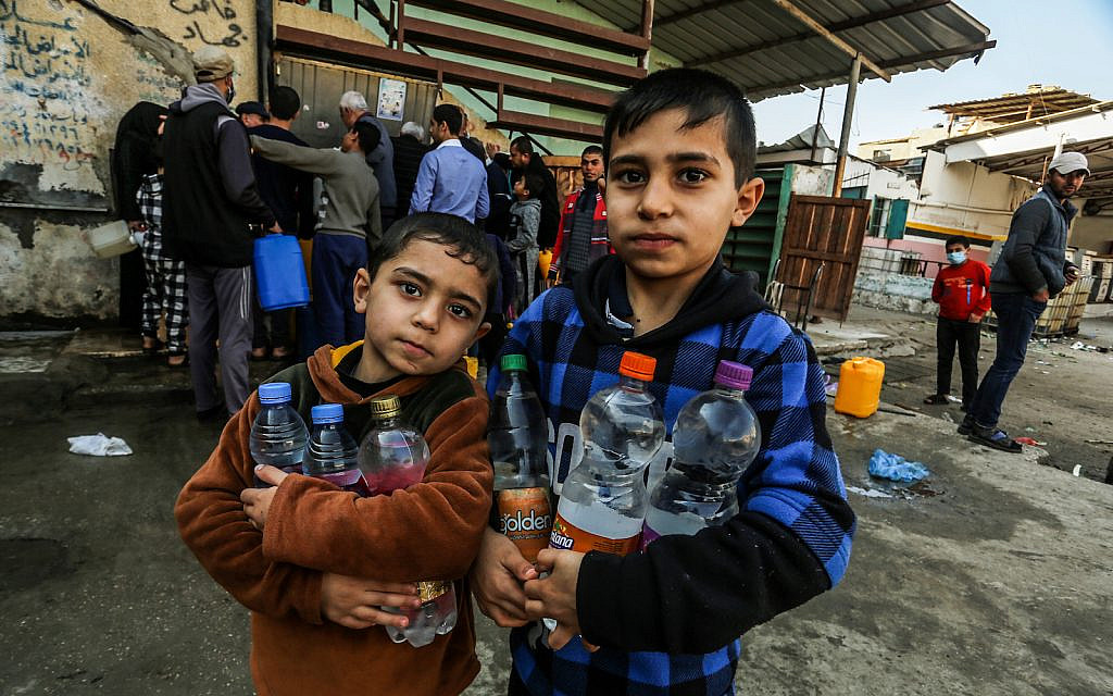 Palestinians fill water from pipes provided by the United Nations Relief and Works Agency (UNRWA) headquarters in the Rafah refugee camp, Southern Gaza Strip, on January 10, 2021. (Abed Rahim Khatib/ Flash90)