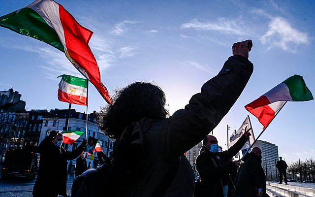People gesture and wave former flags of Iran as they protest outside the Antwerp criminal court during the trial of four persons including an Iranian diplomate and Belgian-Iranian couple in Antwerp, on February 4, 2021. - A Belgian court returns a verdict on February 4, 2021, in the trial of an Iranian diplomat accused of plotting a bomb attack against opposition activists meeting in France. Assadollah Assadi, a 49-year-old formerly based in Vienna, faces up to 20 years in prison if convicted of plotting to target the June 30, 2018 rally. The gathering in Villepinte outside Paris included senior leaders of the exiled National Council of Resistance in Iran (NCRI) and some high-profile supporters. (Photo by DIRK WAEM / BELGA / AFP) / Belgium OUT (Photo by DIRK WAEM/BELGA/AFP via Getty Images)