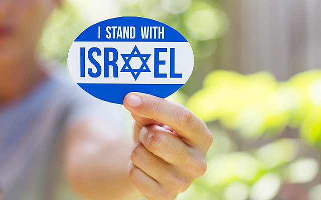Hand holding I stand with Israel sticker