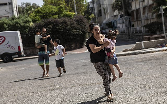 Lia Tal, 40, rushes with her children and partner to take shelter as a siren sounds a warning of incoming rockets fired from the Gaza Strip, in Ashdod, Israel, on May 20, 2021. (AP Photo/Heidi Levine)