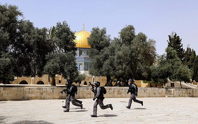 Israeli security forces run during clashes with Palestinians at the compound that houses Al-Aqsa Mosque, known to Muslims as Noble Sanctuary and to Jews as Temple Mount, in Jerusalem's Old City May 21, 2021. REUTERS/Ammar Awad