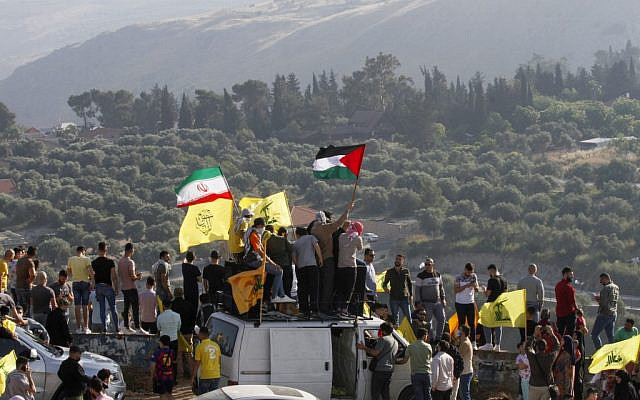 Supporters of Lebanon's Hezbollah lift its flags (C) alongside those of Iran (L) and Palestine, during an anti-Israel protest in the southern Khiam area by the border with Israel, facing the northern Israeli town of Metulla, on May 14, 2021. (Mahmoud ZAYYAT / AFP)