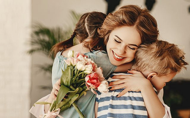 A smiling mother hugs her son and daughter, holding flowers they've given her. (iStock)