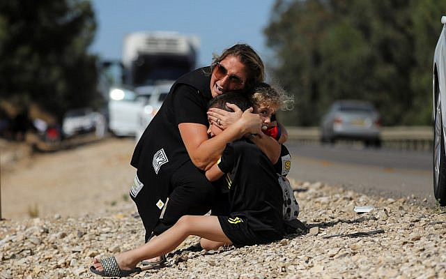A woman protects her children as sirens sound following rocket launched from the Gaza Strip towards Israel near Sderot, Israel May 19, 2021. REUTERS/Ammar Awad