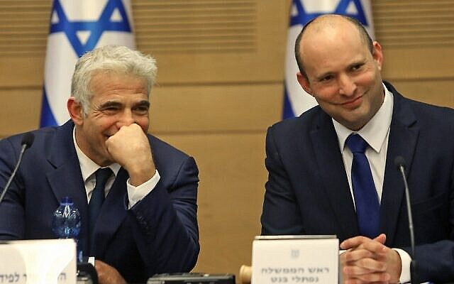 (R to L) Israel's incoming Prime Minister Naftali Bennett and Alternate Prime Minister and Foreign Minister Yair Lapid look on during an address at the Knesset in Jerusalem on June 13, 2021. - Featuring Israeli political veterans and a record number of female lawmakers, a motley coalition including two left, two centre, one Arab Islamist and three right-wing parties came to power Sundayin an eight-party alliance united by animosity for outgoing prime minister Benjamin Netanyahu. (Photo by Gil COHEN-MAGEN / AFP)