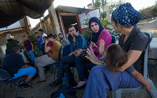 Israeli Jews and Palestinians talk to each other, during a weekly meeting organized by Ali Abu Awwad, a Palestinian from the West Bank, on July 22, 2015. Ali organizes meetings between Jews and Palestinians at his home, to promote cooperation and co-existence. (Nati Shohat/Flash90/File)
