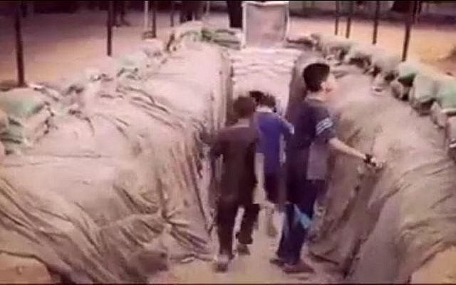 An image taken from a video on Hamas's Facebook page on July 20, 2016, shows Palestinian children entering into a tunnel dug by the terror group in the Gaza Strip. (Screen capture from Facebook/File)