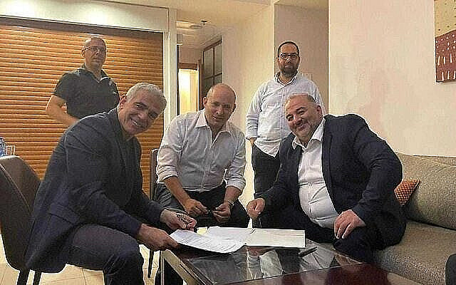 Yesh Atid leader Yair Lapid (L), Yamina leader Naftali Bennett (C) and Ra'am leader Mansour Abbas sign a coalition agreement on June 2, 2021. (Courtesy of Ra'am)
