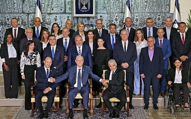 Outgoing Israeli President Reuvin Rivlin (C) is flanked by Prime Minister Naftali Bennett (L) and alternate Prime Minister and Foreign Minister Yair Lapid during a photo with the new coalition government, at the President's residence in Jerusalem, on June 14, 2021. - A motley alliance of Israeli parties on June 13 ended Benjamin Netanyahu's 12 straight years as prime minister, as parliament voted in a new government led by his former ally, right-wing Jewish nationalist Naftali Bennett. (Photo by EMMANUEL DUNAND / AFP)