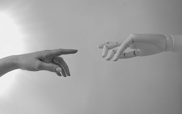 Illustrative image of a human hand and a robot, Artificial Intelligence (AI); (Photo Credit: Tara Winstead from Pexels)