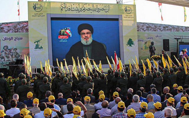 Supporters of the Shiite Hezbollah terror group gather to watch the transmission on a large screen of a speech by the movement's leader Hassan Nasrallah, in the town of Al-Ain in Lebanon's Bekaa valley on August 25, 2019. (AFP)
