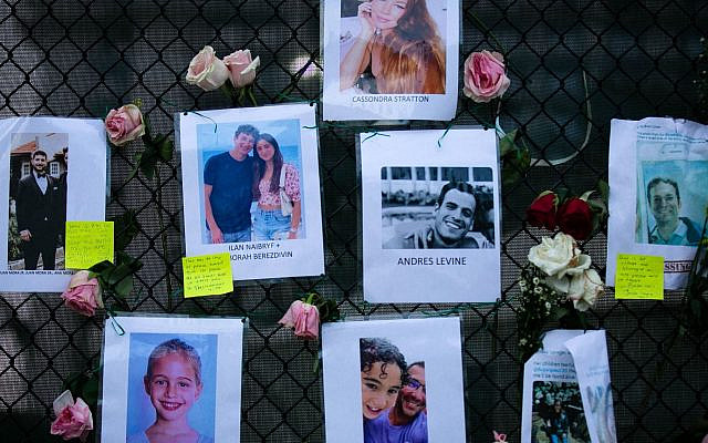Images of Andres Levine, Ilan Naibryf and Deborah Berezdivin, three of the Jewish victims of the Surfside building collapse, in center among other photographs of those missing posted at a makeshift memorial on the building site in Surfside, Fla., June 26, 2021. (Andrea Sarcos/AFP)