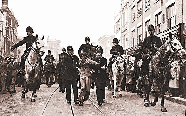 A demonstrator is taken away under arrest by police officers after a mounted baton charge, in East London, on Oct. 4, 1936, to stop fighting between anti-fascists and Sir Oswald Mosley's blackshirts. Via Jewish News