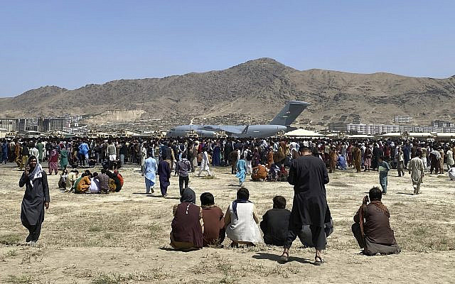 Hundreds of people gather near a US Air Force C-17 transport plane at a perimeter at the international airport in Kabul, Afghanistan, August 16, 2021. Thousands of Afghans trapped by the sudden Taliban takeover rushed the tarmac and clung to US military planes deployed to fly out staffers of the US embassy, which had shut down. (AP Photo/ Shekib Rahmani)