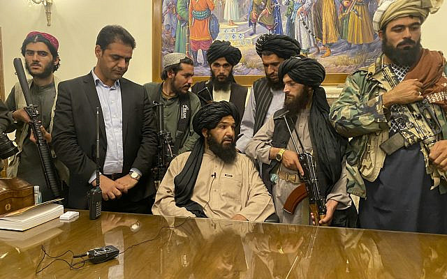 Taliban fighters take control of the Afghan presidential palace, after the Afghan President Ashraf Ghani fled the country, in Kabul, Afghanistan, on August 15, 2021. The man standing second from left is a former bodyguard for Ghani. (AP Photo/Zabi Karimi)