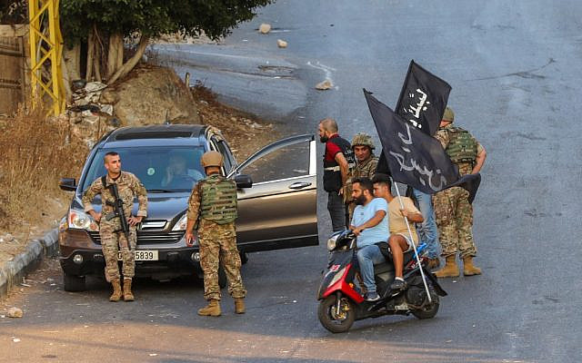 Hezbollah supporters carrying flags on motorbikes drive past Lebanese soldiers as the army deploys amid clashes in the Khalde area, south of the capital, on August 1, 2021 (ANWAR AMRO / AFP)