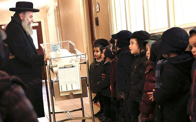 Illustrative: School children pray with a recently born child at Aishes Chayil, a postpartum recovery center, in Kiryas Joel. N.Y. Feb. 16, 2017 (AP Photo/Seth Wenig)
