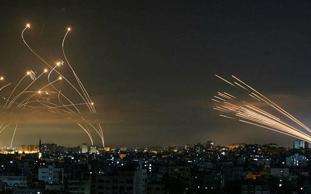 May 2021: On the right, incoming rockets fired by terrorists in Gaza. On the left, Iron Dome in action. (Anas Baba/AFP via Getty Images)
