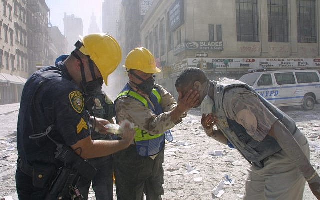 Police officers help rinse a man's eyes after the fall of the Twin Towers on September 11, 2001, in New York City. (AP Photo/ Shawn Baldwin)