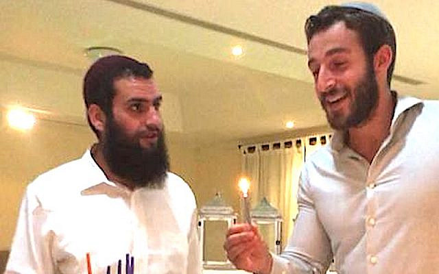 Lighting Hannukah candles in Dubai that first time with Rabbi Levi Duchman (left). (Courtesy)