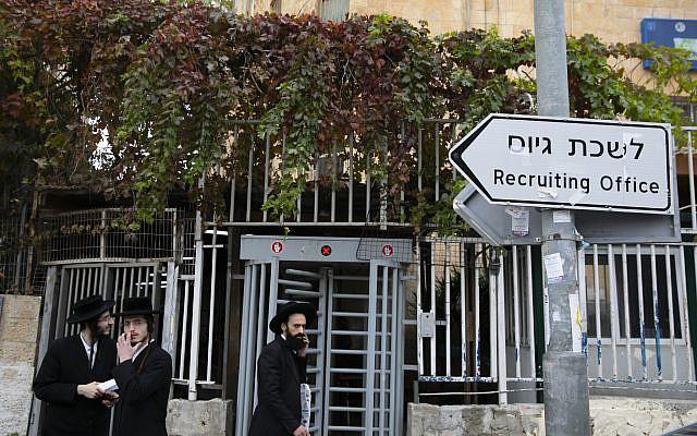 Ultra-Orthodox men walk outside the IDF recruitment office in Jerusalem, on December 5, 2019. (Olivier FitoussiFlash90)
