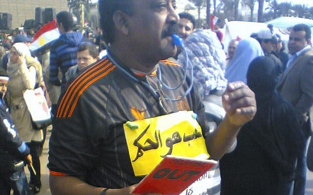"""Photo in February 2011 taken by Khalid, in Tahrir Square in Egypt. The individual in the photo is dressed like a referee and has a sign that reads """"the people are the referee""""."""