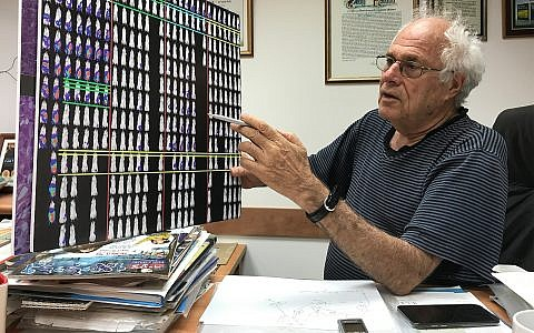 Weizmann Institute's Prof. Zelig Eshhar holds a  board that illustrates how the cancer treatment works with mice. Aug. 29, 2017  (Shoshanna Solomon/Times of Israel)