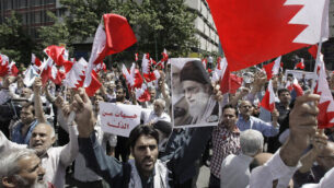 """Iranians wave Bahraini flags as they chant slogans during a demonstration in Tehran, Iran, Friday, May 18, 2012. Iranians rallied Friday to denounce efforts by Bahrain's Sunni rulers to forge closer ties with Saudi Arabia, a pact the Shiite powerhouse Iran claims would go against the will of the tiny island nation's majority Shiites. A man holds a poster of Iranian supreme leader Ayatollah Ali Khamenei, center right, and Arabic on the poster, center left, reads, """"enough of humiliation."""" (AP Photo/Vahid Salemi)"""