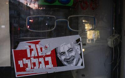 تصویر: بر روی پوستری با تصویر بنیامین نتانیاهو نخست وزیر بر روی ویترین یک فروشگاه تعطیل در تل آویو نوشته «بخاطر من بسته شده»، ۱۳ اکتبر ۲۰۲۰. (AP Photo/Ariel Schalit)