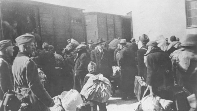 """عکس از موزه هولوکاست ایالات متحده . الکساندر بولو، مرکز، رو به دوربین، صاحب منصب بلغاری """"مساله یهود"""" در حال نظارت به اخراج یهودیان مقدونی از یوگسلاوی تحت اشغال بلغارستان، در مارچ 1943. سربازان آلمانی در سمت چپ ایستاده اند. آرشیوی از هزاران سند علیه جنایتکاران جنگی جنگ جهانی دوم، از هیتلر تا دست اندرکاران عادی هولوکاست که هرگز محاکمه نشدند برای اولین بار در موزه هولوکاست واشنگتن در معرض تماشای عموم قرار داده می شود. این اسناد در ده های گذشته در اختیار سازمان ملل و به صورت محرمانه نگاه داشته شدند."""