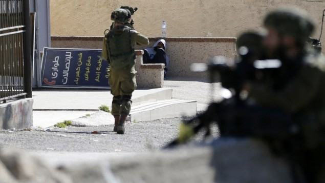 سرباز نیروی دفاعی، پیش از بازداشت تظاهرکننده فلسطینی، در کمپ پناهندگی عماری نزدیک رمله در کرانه باختری، ۱۵ ژانویه ۲۰۱۶، تفنگ خود را به سوی وی نشانه رفته است