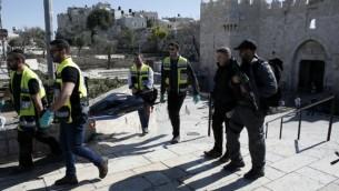 داوطلبان یهودی ذکا، جسد مرد فلسطینی که در پی چاقوزنی به سه نفر بیرون دروازه دمشق اورشلیم به ضرب گلوله کشته شد را از صحنه خارج می کنند  - خبرگزاری فرانسه