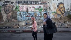 زنان فلسطینی در حال عبور از مقابل دیوارنگاری رئیس سازمان آزادیبخش فلسطین، یاسر عرفات، و رهبر زندانی تنظیم، مروان برقوت در ایست بازرسی قلندیه - یوناتان سیندل