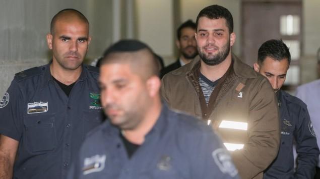 متهم به ترور، بیلال ابو قانم به همراه پلیس زندان در دادگاه منطقه اورشلیم، ۱۳ مارس ۲۰۱۶ - یوناتان سیندل