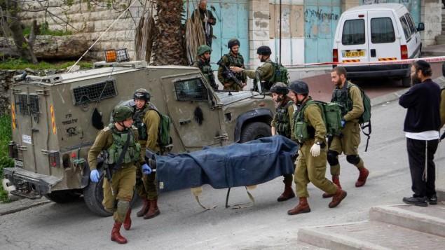 سربازان اسرائيلی پیکر مرد فلسطینی که به سربازی در حبرون، کرانه باختری، ۲۴ مارچ ۲۰۱۶ چاقو زد را از محل حادثه خارج می کنند. مرد فلسطینی بلافاصله پس از چاقوزنی و مجروح کردن سرباز اسرائيل مورد شلیک گلوله قرار گرفته بوده است. ویسلام هاشلامون