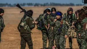 زنان رزمنده کورد در واحد یگان های مدافع خلق، در حال حمل سلاح های خود پیش از حمله ای علیه جنگجویان دولت اسلامی در نزدیکی روستای مبروکه، شمال شرقی سوریه